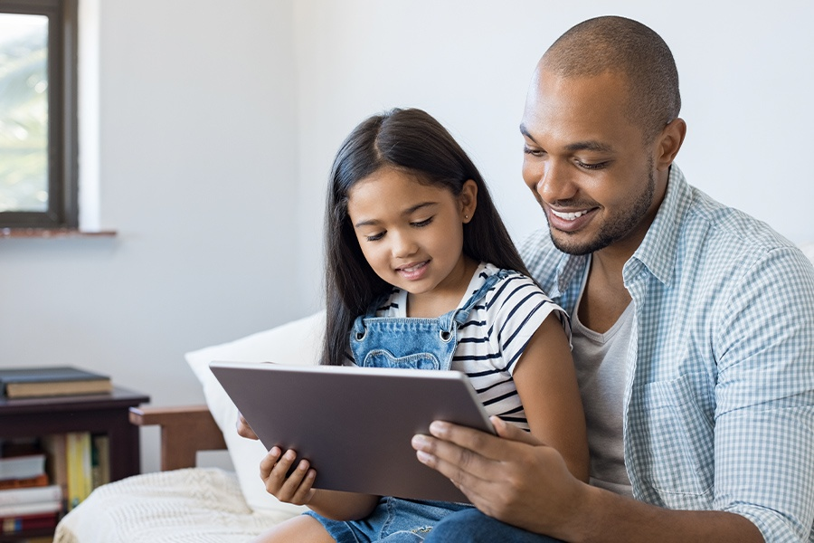 Blog - Father and Daughter Using a Tablet Together While Sitting on the Sofa