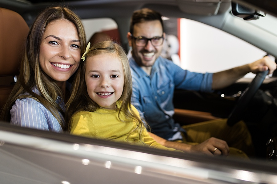 Personal Insurance - Happy Family Buying a New Car at the Car Showroom